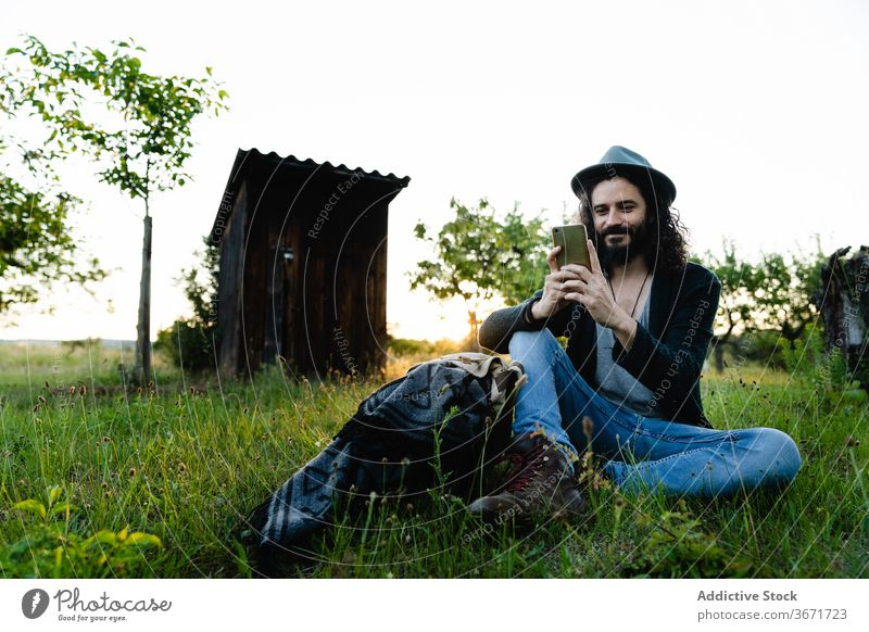 Relaxed man browsing smartphone on meadow hipster social media chat field summer relax using male nature weekend green happy cheerful internet rest connection