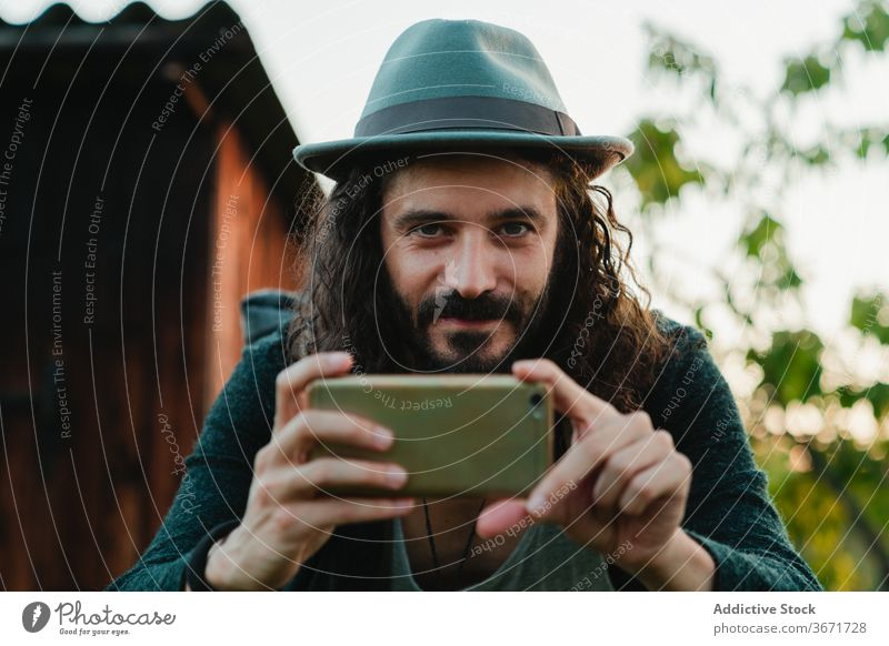 Traveling man using smartphone in countryside hipster browsing travel rural nature tourism male mobile surfing style beard trendy backpack smile content guy