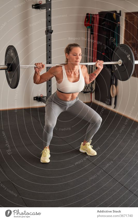 Strong female athlete squatting with barbell sportswoman healthy workout motivation weightlifting wellbeing power energy activity vitality physical fitness
