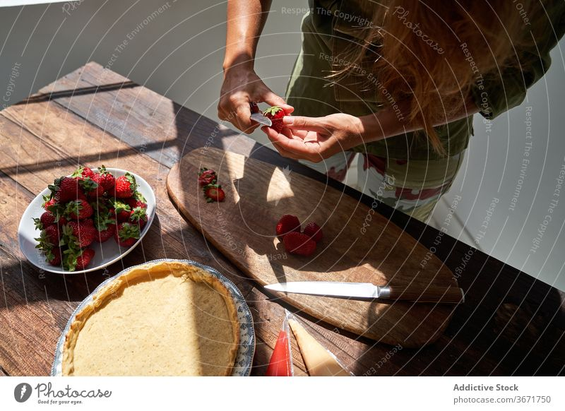 Crop housewife preparing delicious pie at home cook homemade cake woman kitchen dessert peel strawberry prepare female product process fresh recipe pastry table