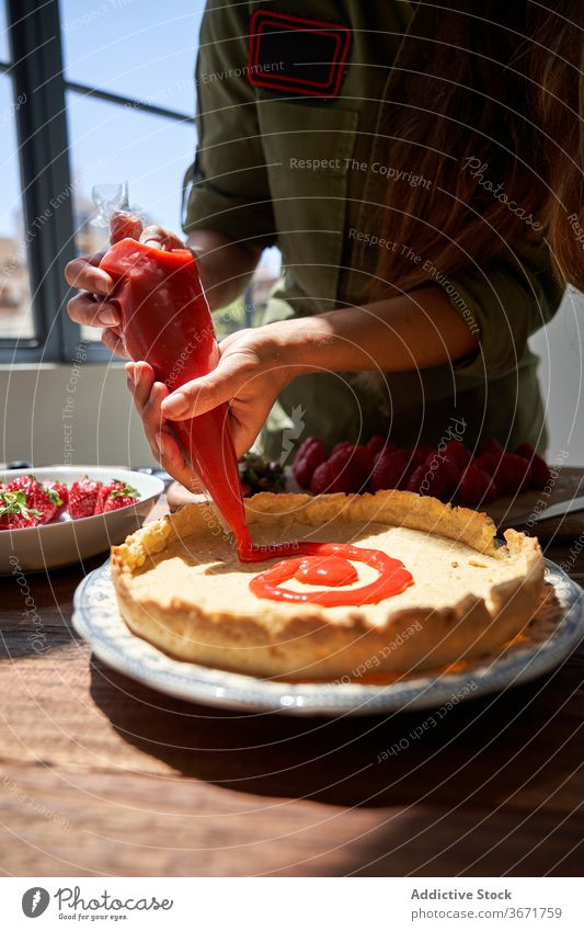 Crop woman decorating cake with cream piping bag squeeze pie cook decorate confectionery homemade female delicious table housewife food yummy palatable sweet