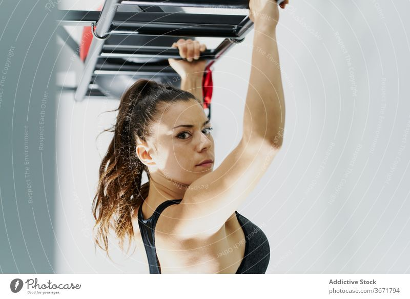 Confident fit woman doing exercises in gym workout pull up active sportswoman focus confident athlete female sportswear fitness slim bra modern wellness
