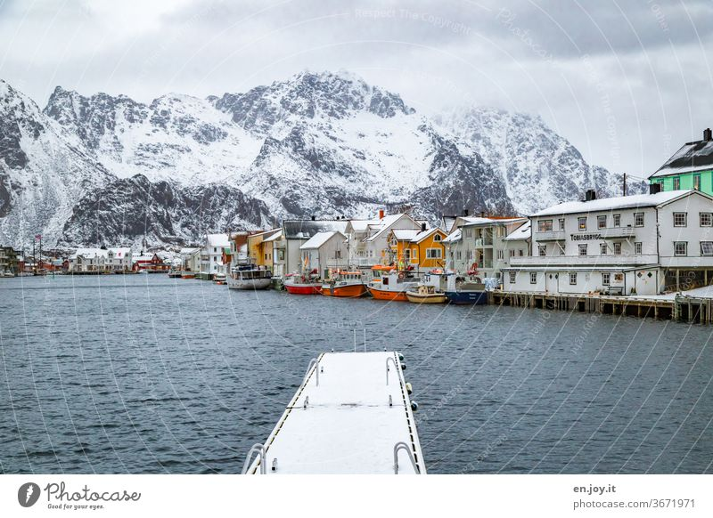 Nordic small town on the fjord with fishing boats and jetty in front of snowy mountains Henningsvær Lofotes Norway Fishing village Footbridge landing stage Snow