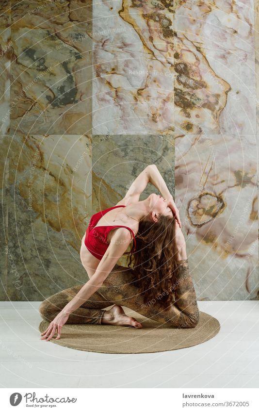 Young brunette woman in red top practicing One-legged King Pigeon Pose (eka pada rajakapotasana) indoors yoga yogini sport athlete slim female young meditation