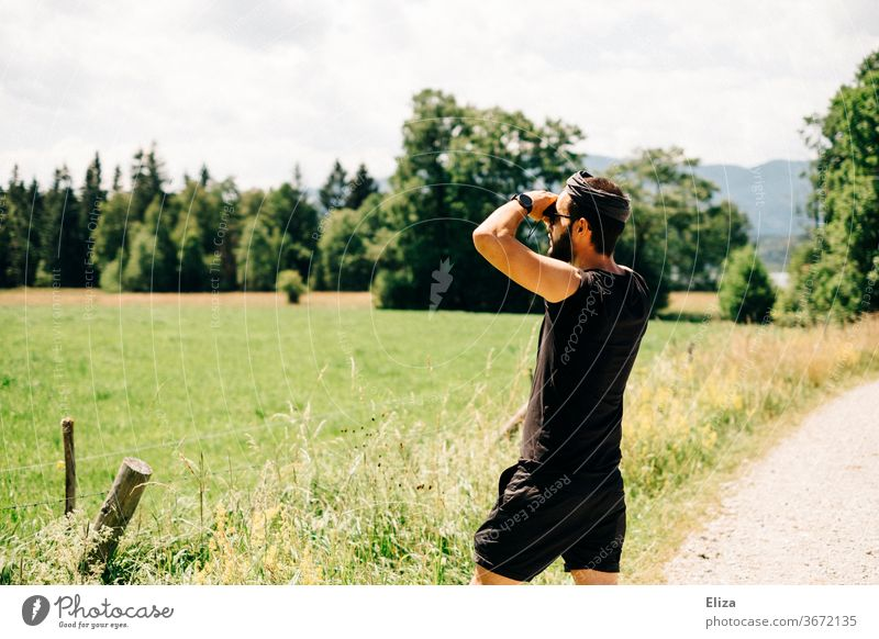 Man observes something through binoculars in nature Binoculars Observe Nature search Adventure Landscape Summer Far-off places Looking Discover Vantage point