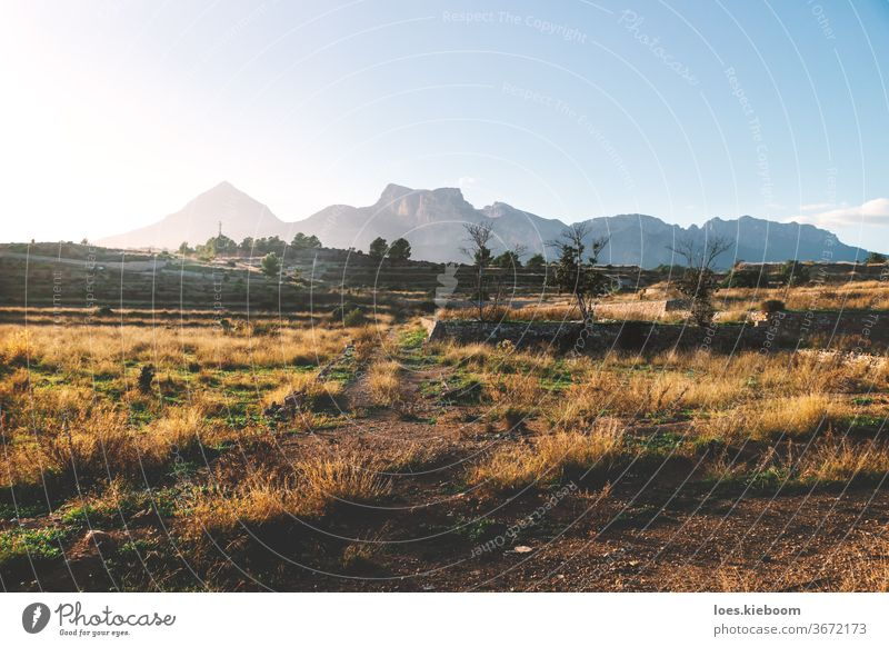 Former farmland on the countryside of Costa Blanca during sunset with lit mountains, La Nucia, Spain travel nature landscape desert rock wasteland hill spain