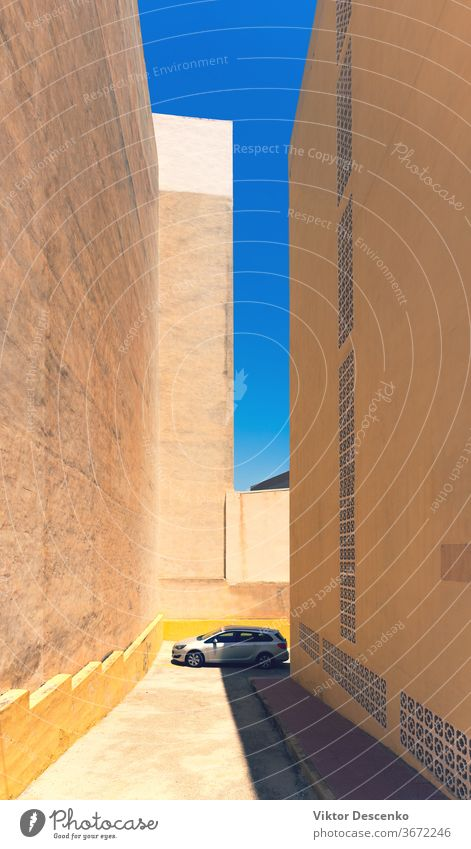 The car is parked on a summer day among the buildings spain tall hot house architecture city town street sky outdoor transport europe urban view blue travel