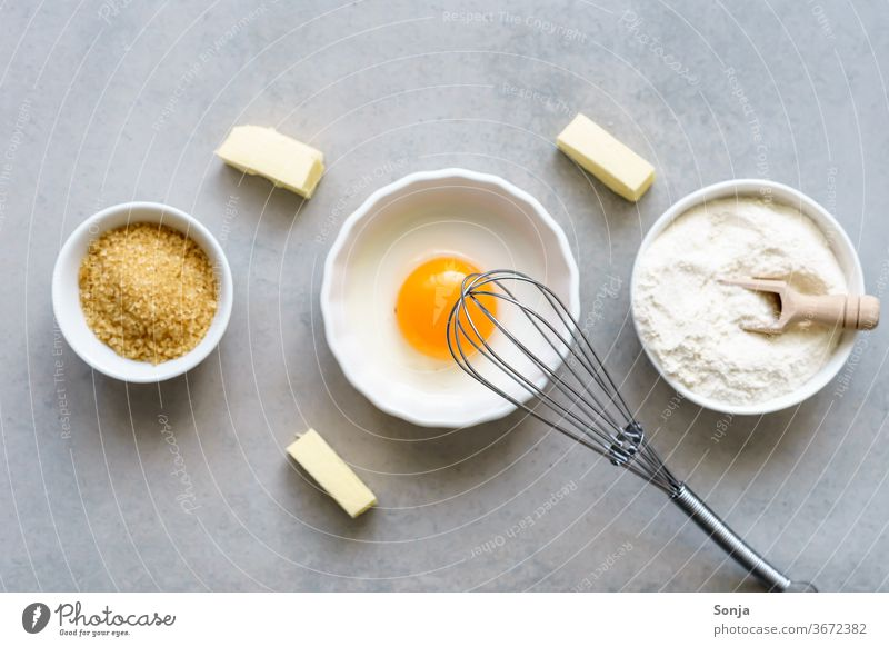 Egg yolks, flour and sugar in three white bowls. Baking ingredients for cakes, top view. Ingredients Flour Sugar Table Cake Rustic Dough Food Whisk Butter