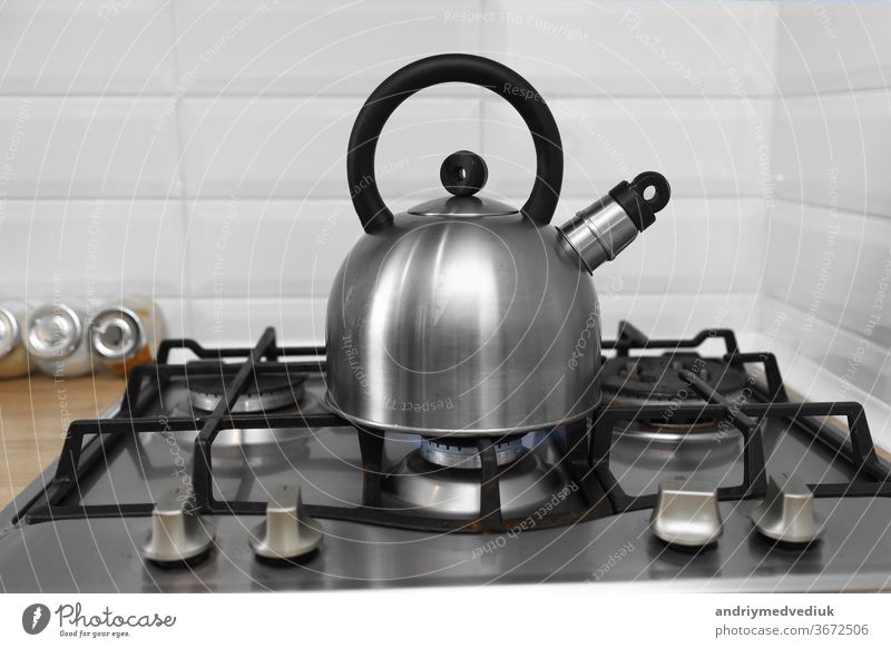 metal kettle on a gas stove. kettle boiling on a gas stove. Focus on a spout. Tea kettle with boiling water on gas stove steam steel kitchen hot cooking