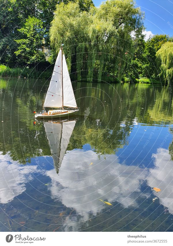A model sailing boat sailing on a pond on a summer day Sail Sailboat Model-making Clouds in water Summer graze Miniature Sailing