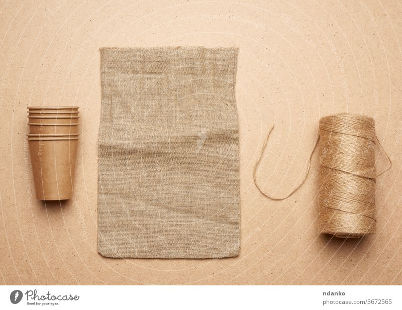 paper cup, skein with brown rope and empty bag on a brown wooden background concept accessory backdrop beige blank burlap canvas closeup cloth container design