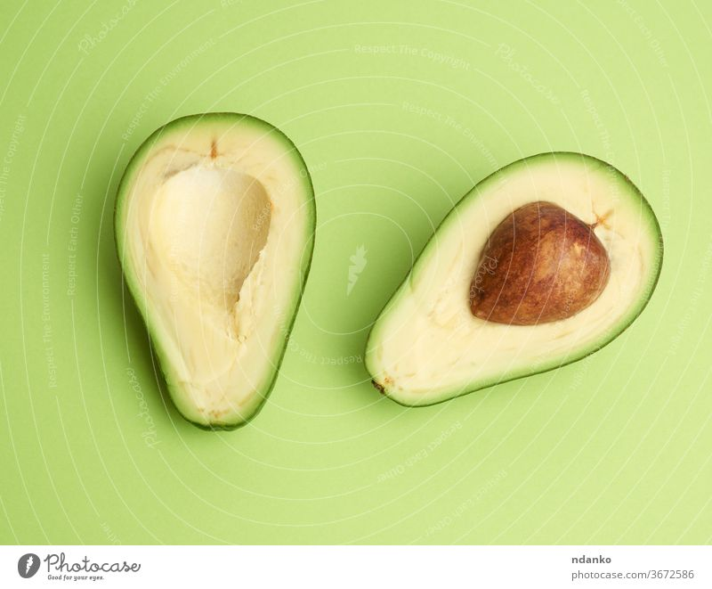 half ripe green avocado with a brown pit on a green background clipping closeup color cooking core cut delicious diet dieting eating exotic food fresh freshness