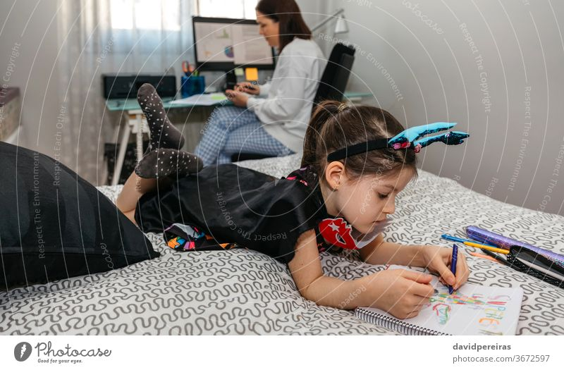 Girl drawing in disguise while her mother teleworking home office work family reconciliation girl bedroom covid-19 coloring telecommuting life balance 2019-ncov