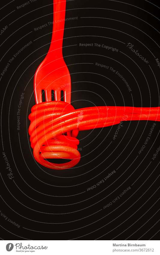 Spaghetti new defined. Hot red spaghetti on a red fork on black background swirls copy space art food dinner cuisine pasta isolated healthy meal gourmet