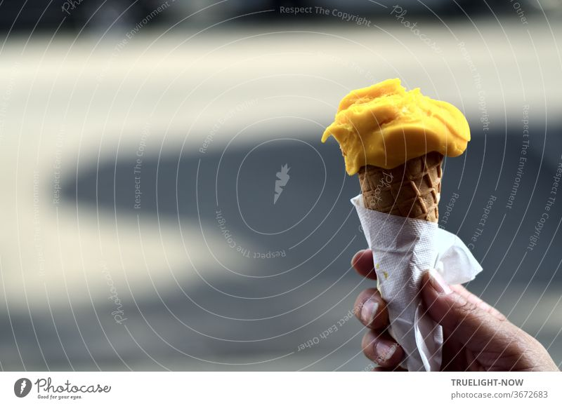 If the weather is nice and hot - all children want ice cream: Mango - Mango! Schleck - Schleck! A woman's hand holding an ice cream cone with a ball of yellow mango ice cream with a paper napkin in front of light and shadow on the street