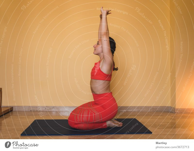 Fit young girl doing yoga at home by covid confinement. Young woman in sportswear stretching her arms while sitting on her legs on the mat in the cozy living room at home.