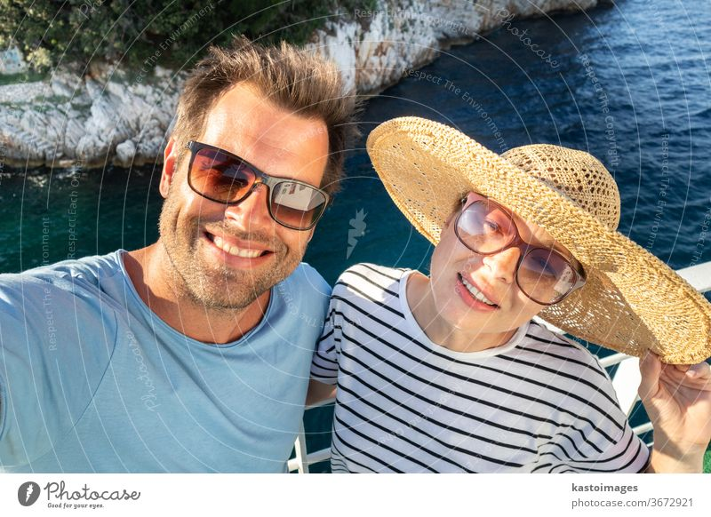 Beautiful, romantic caucasian couple taking selfie self portrait photo on summer vacations traveling by cruse ship ferry boat. lifestyle love straw hat guy girl