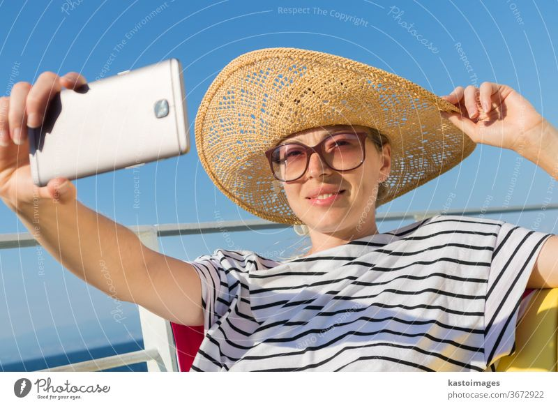 Beautiful, romantic blonde woman taking selfie self portrait photo on summer vacations traveling by cruse ship ferry boat. girl cruise ocean happy nautical