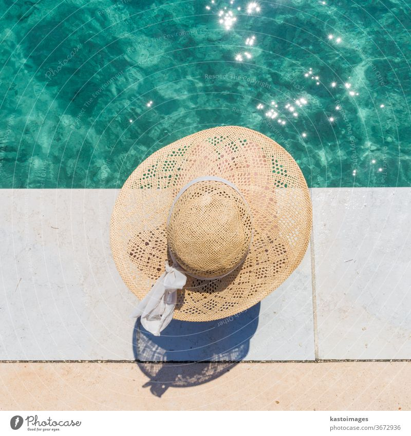 Woman wearing big summer sun hat relaxing on pier by clear turquoise sea. water leisure beauty girl person blue tan body young spa pool woman beach holiday
