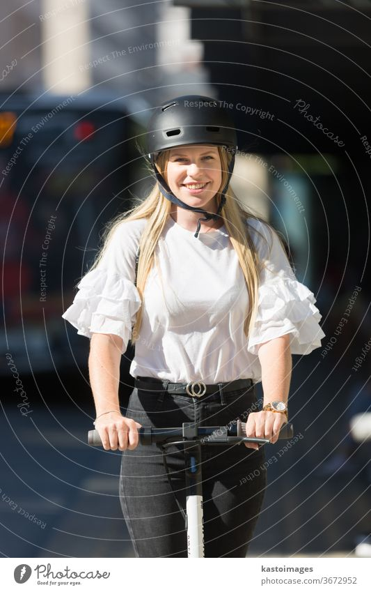 Trendy fashinable teenager, beautiful blonde girl riding public rental electric scooter in urban city environment. Eco-friendly modern public city transport
