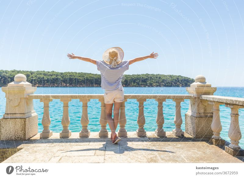 Rear view of happy woman on vacation, wearing straw summer hat ,standing on luxury elegant old stone balcony of coastal villa, relaxing, arms rised to the sun, looking at blue Adriatic sea.