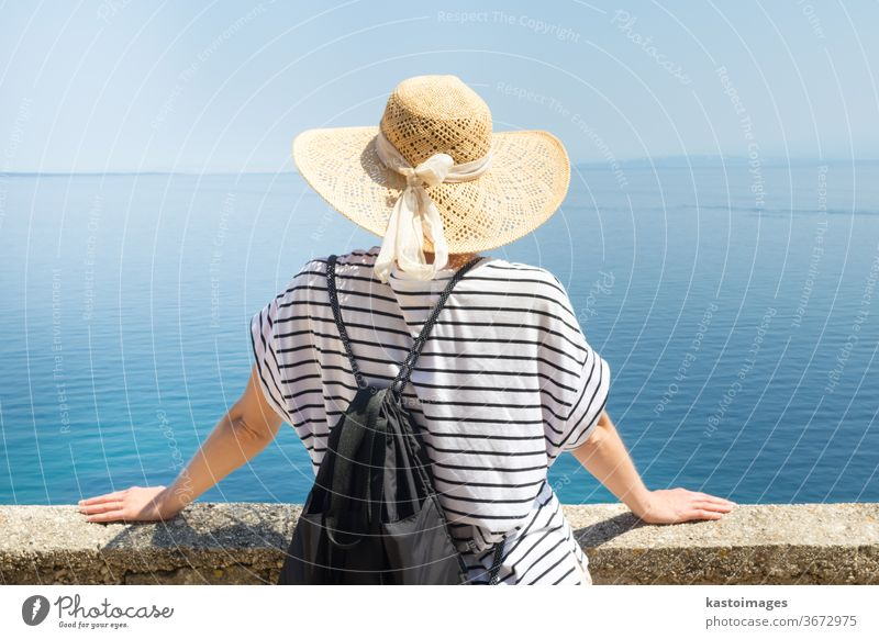 Rear view of a traveller wearing a straw hat and rucksack, leaning against a stone wall and looking out over the big blue sea and the islands on the horizon. Copy space.