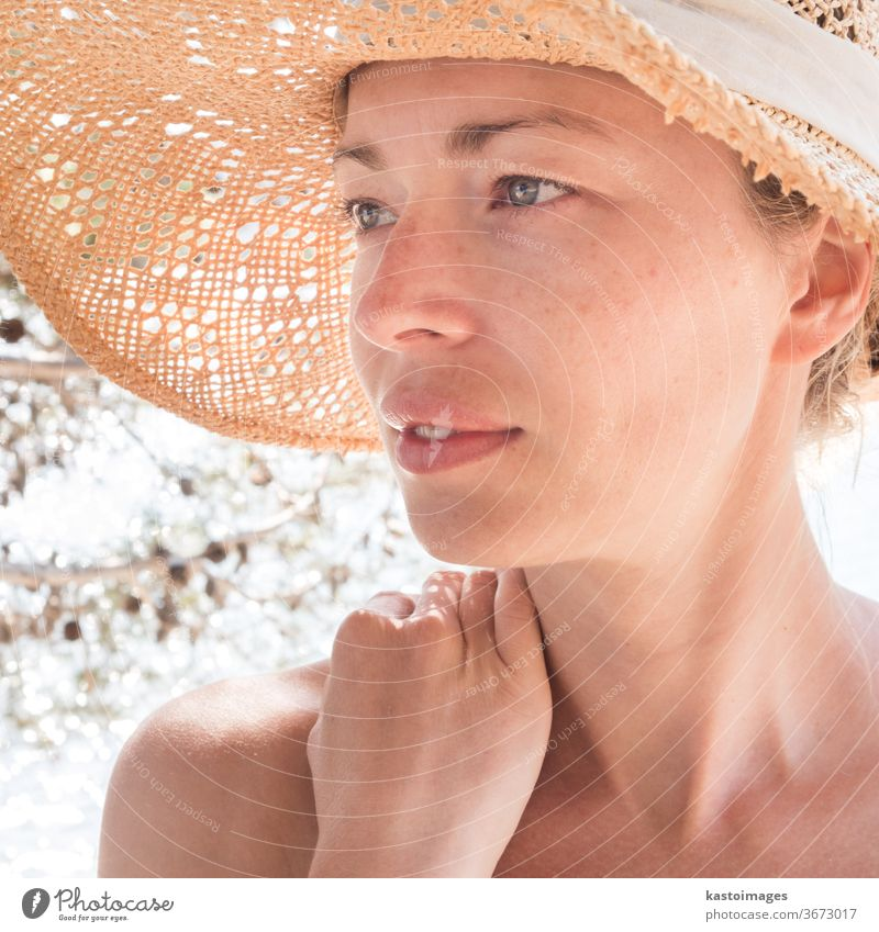 Close up portrait of no makeup natural beautiful sensual woman wearing straw sun hat on the beach in shade of a pine tree. summer person female lady young sea