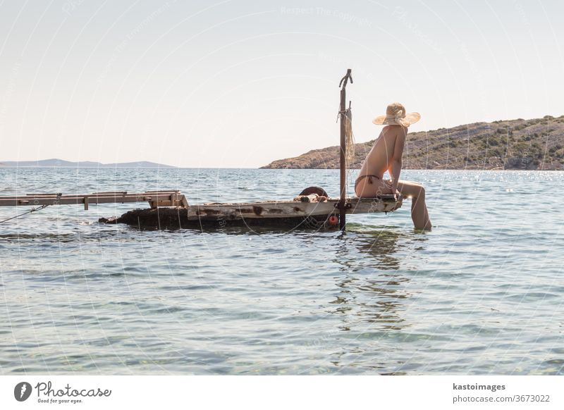 View of unrecognizable woman wearing big summer sun hat tanning topless and relaxing on old wooden pier in remote calm cove of Adriatic sea, Croatia. leisure