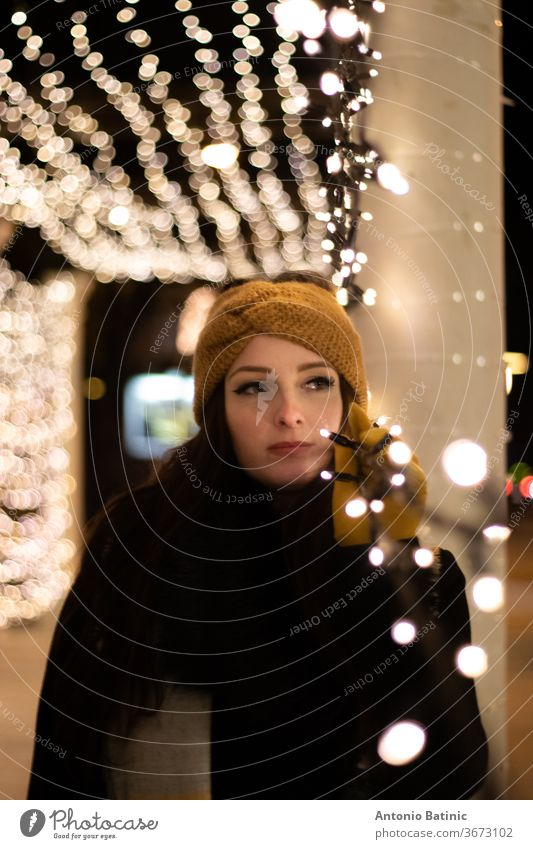 Night portrait of a young woman looking into the distance , leaning on a string of christmas lights. Cold winter night smile bokeh girl beautiful female evening