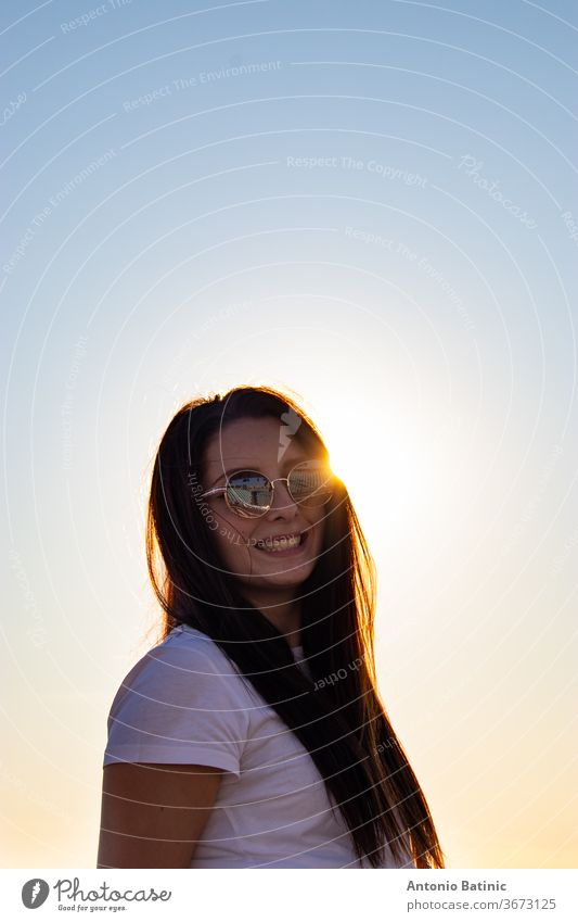 Attractive brunette with sunglasses laughing , sun directly behind her head peeking, golden sunset hour. attractive background beautiful beauty casual caucasian