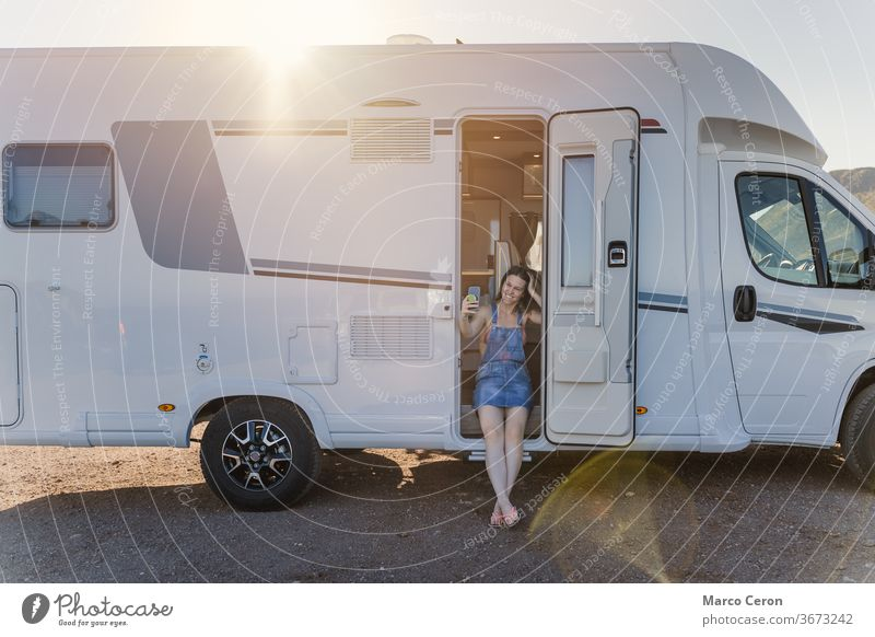 Smiling Young woman taking a selfie on her motor home parked on the beach on a sunny day smiling lifestyles young van desert exploration journey camper van