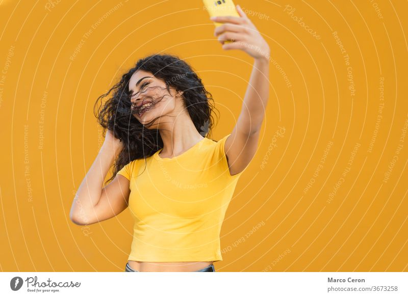young mixed race woman inyellow t-shirt making a funny selfie with her phone with orange wall in the background taking smartphone lifestyle laisure activity