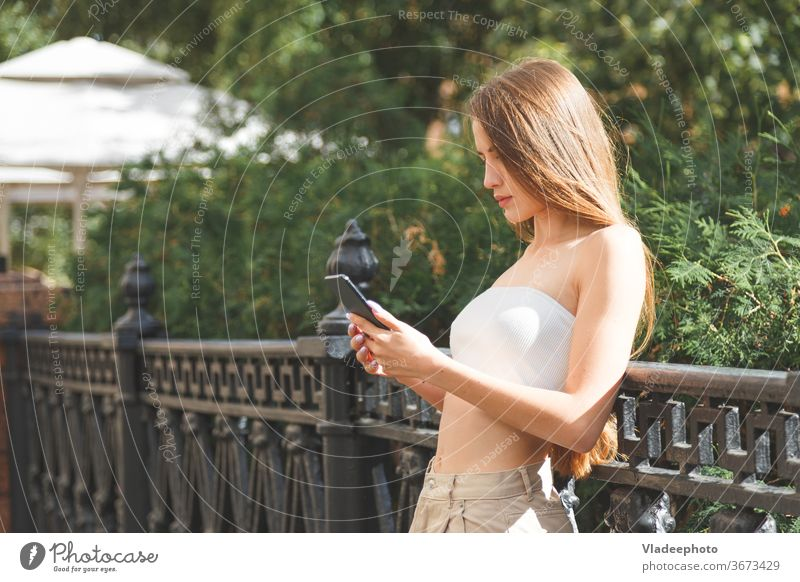 Young stylish pretty woman with smartphone in the city streets. young hat europe technology happy girl female urban people smiling casual lifestyle cellular