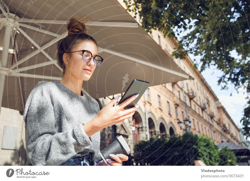 Young stylish pretty woman with smartphone at the outdoor cafe. young city internet public eyeglasses outdoors portrait casual style lifestyle female girl