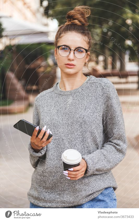 Young girl dressed in casual clothes with smartphone and a cup of takeaway coffee. Daily life of youth. People online woman young city internet public