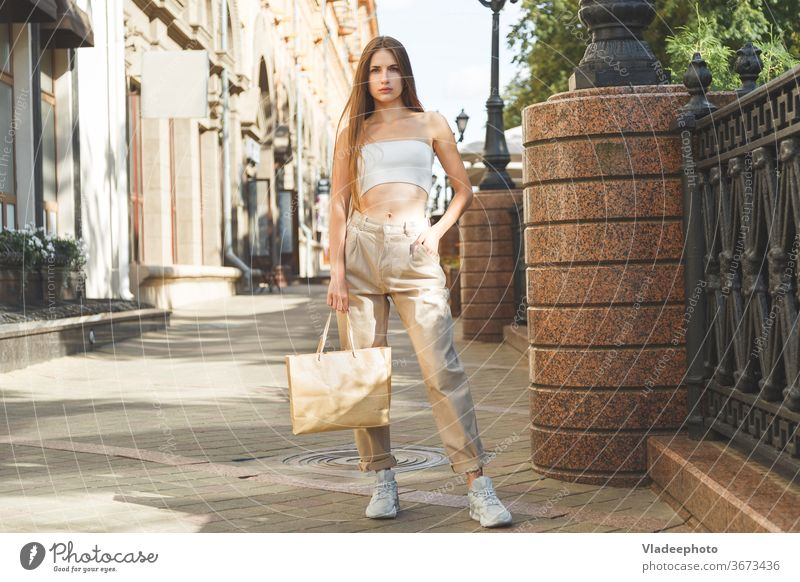 Beautiful caucasian fashionly dressed girl standing outdoors with paper bag with purchases in the city. beautiful shopping woman young female jeans pants top