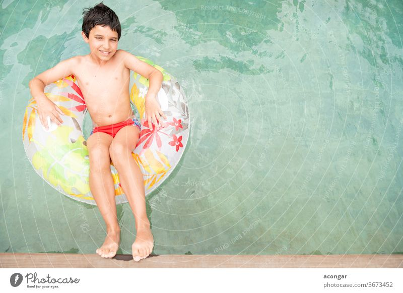 Boy floating on an inflatable circle in the pool. Child blue boy carefree caucasian childhood comfortable cool cute enjoyment float tube flower fun happiness