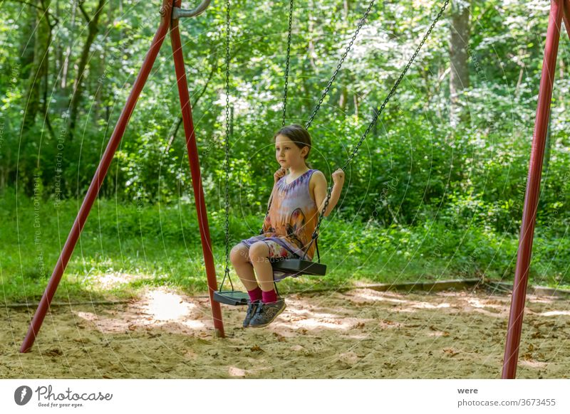 Little girl on a swing in the forest Child Playing Joy Summer Movement Playground Toddler feet motor function Schoolyard Meadow Play instinct Infancy Gymnastics