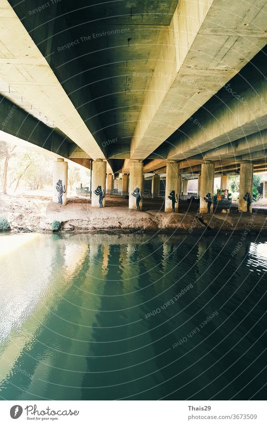 Green river water under the bridge cement construction, reflection on water lines engineering structure industry perspective bridge construction silhouette