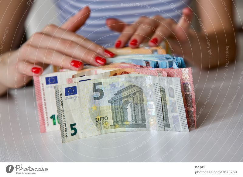 Payday | hands of a young woman and many banknotes standing on the table before her. Bank note Money Euro bill Many figures Arrange Young woman Save Thrifty