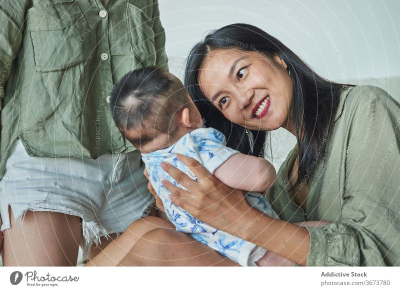 Mother holding her soon and smiling at home family baby child boy dad mom mother fun enjoy stay at home beautiful model portrait flat people happy family