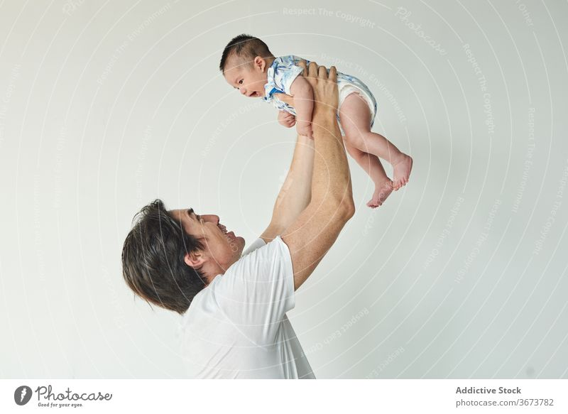 Father lifting up his baby family child soon boy dad father fun enjoy home at home stay at home beautiful model portrait flat people happy family caucasian