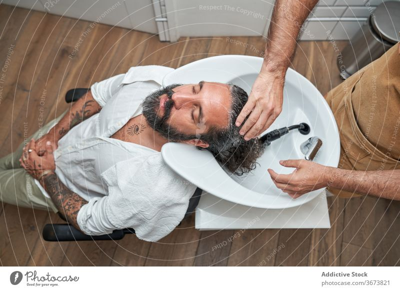 Barber washing hair of male client in salon men barber head sink customer barbershop workplace hairdresser haircut hairstylist service beard care professional