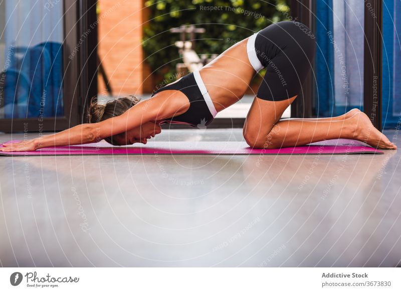 Fit woman stretching back on yoga mat at home practice vitality barefoot health care wellbeing stress relief spirit energy wellness parquet calm slim beauty