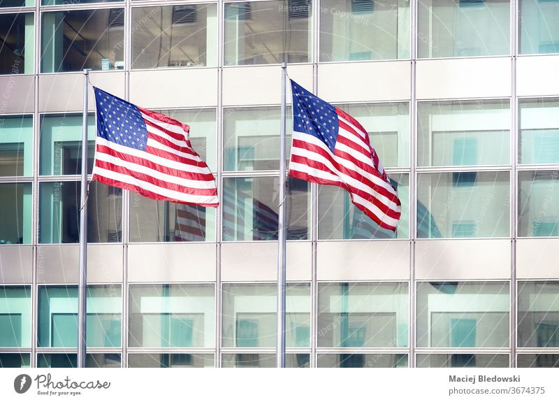 Two American Flags in front of an office building, New York. flag USA skyscraper patriotism urban national freedom waving symbol success stripes stars modern