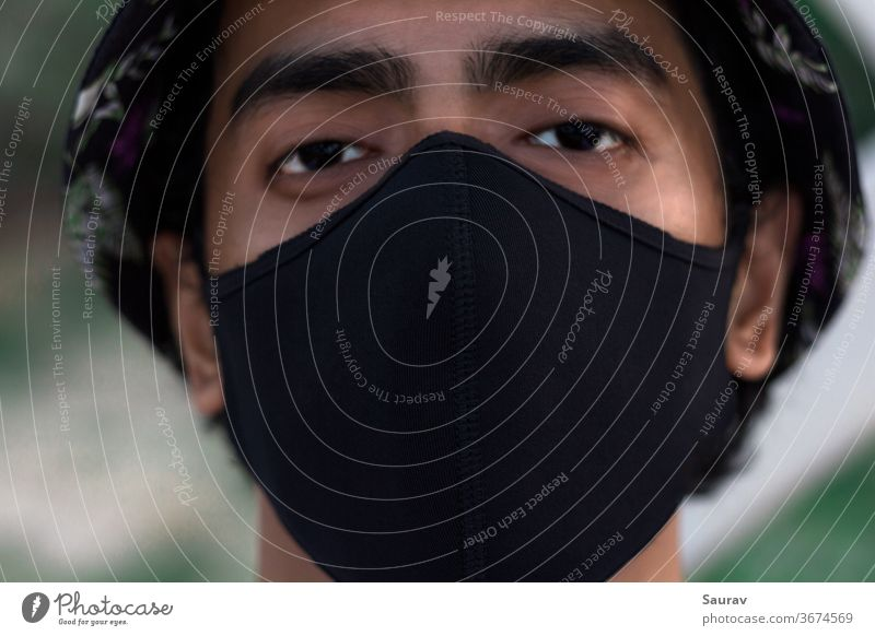 Close Up Portrait of a Young Millennial wearing a Black Protective Mask to Prevent Covid-19 Virus Infection. The New Normal during World Pandemic. new normal