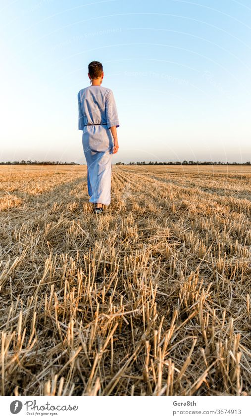 woman farmer walks through a mown wheat field in Ukraine agricultural agriculture authentic autumn back blue bread clothing country countryside crop dress empty
