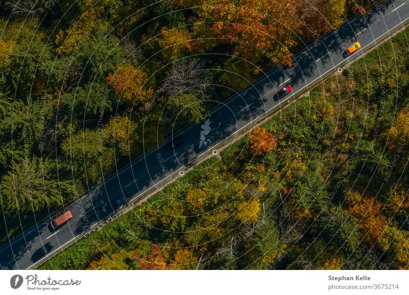 Vertical view from a drone at a autumn road. car speed fall diagonal inspiring sun nature landscape awesome line wonderful copter traffic bavaria breathtaking