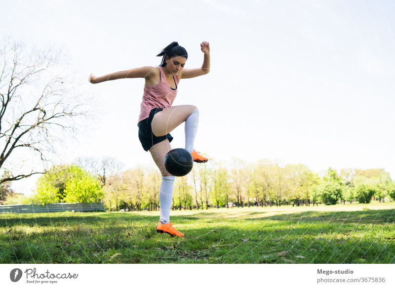 Young female soccer player practicing on field. young woman football focused exercising athleticism trick summer sports activity recreational players