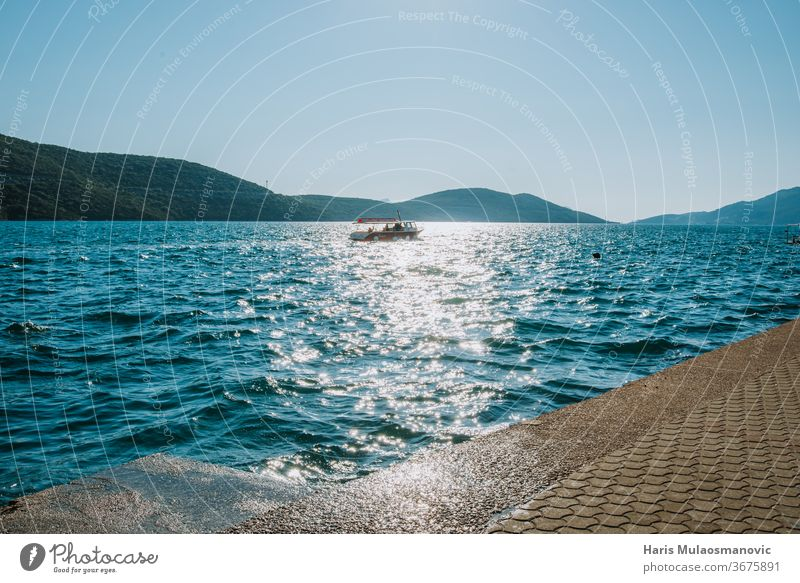 boat sailing in the distance on the sea background beach beautiful blue coast concept europe holiday island landscape mediterranean nature ocean outdoor relax